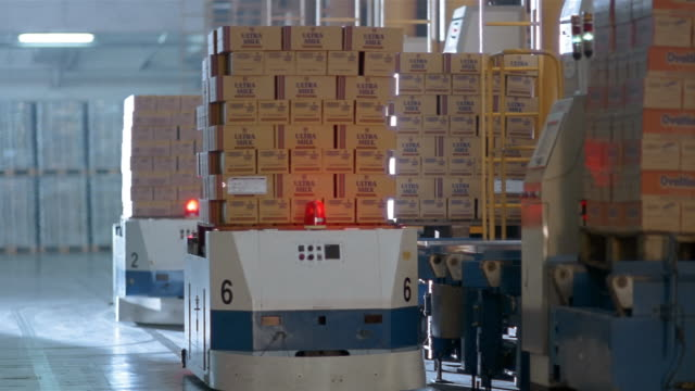medium shot boxes being moved by robotic pallets at warehouse in milk factory - milk box stock videos & royalty-free footage