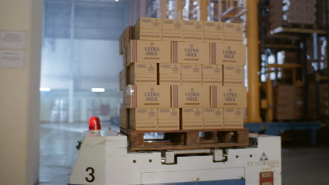 medium shot boxes being moved on robotic pallets in warehouse at milk factory - 段ボール箱点の映像素材/bロール