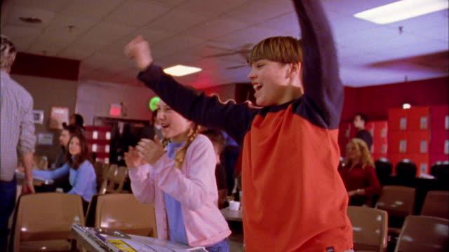 medium shot boy and girl bowling / cheering w/family - human limb stock videos & royalty-free footage