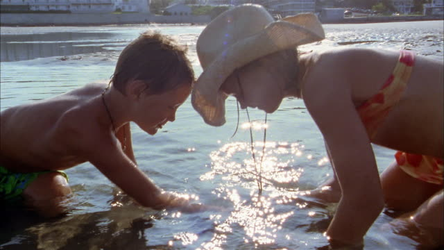 Medium shot boy and girl in straw hat looking in tidepool w/hands in water