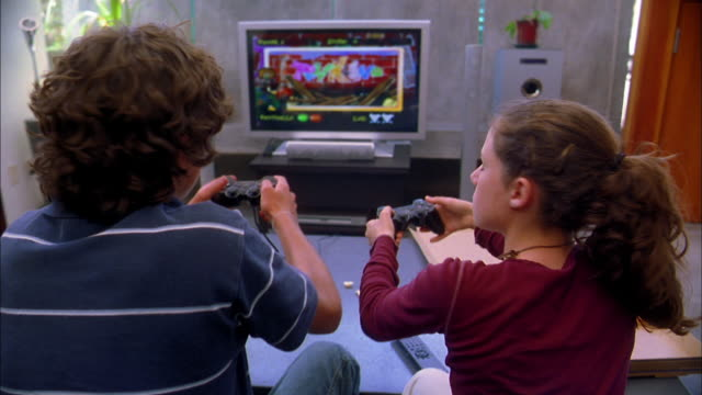 Medium shot  boy and girl playing video game w/view of game screen