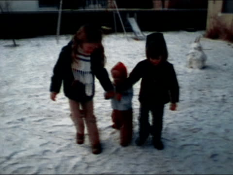 1978 medium shot boy and girl walking and holding hands with baby in snowy yard - children only stock videos & royalty-free footage