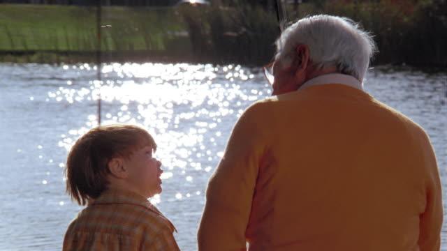 Medium shot boy and grandfather fishing + talking at sun-dappled lake