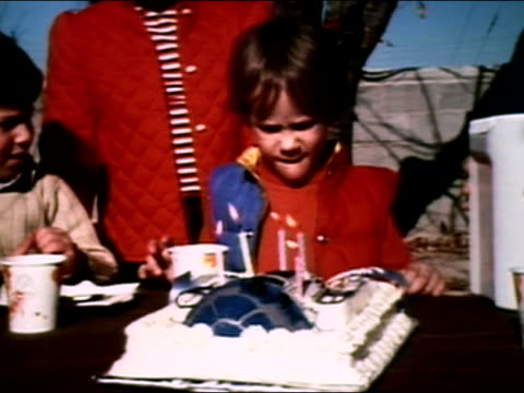1981 medium shot boy blowing out birthday candles on robot cake/ zoom out children around table - barndom bildbanksvideor och videomaterial från bakom kulisserna