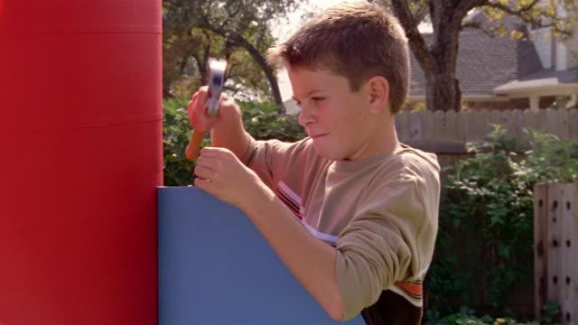 Medium shot boy building large model rocket in backyard