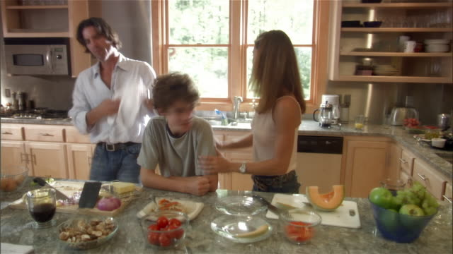 vidéos et rushes de medium shot boy feeding omelette to woman / man tossing grapes into the mouths of family members - raisin