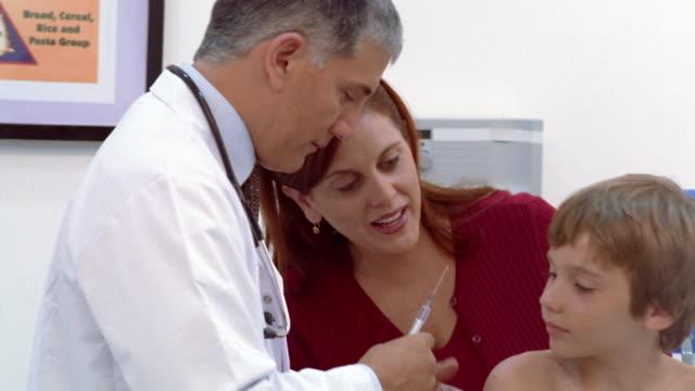 stockvideo's en b-roll-footage met medium shot boy getting a shot in pediatrician's office as mother watches - ontbloot bovenlichaam