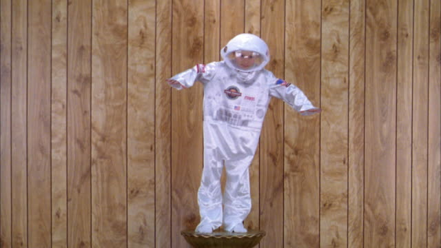 medium shot boy in astronaut space suit costume posing on pedestal w/wood paneling in background - astronaut stock videos & royalty-free footage
