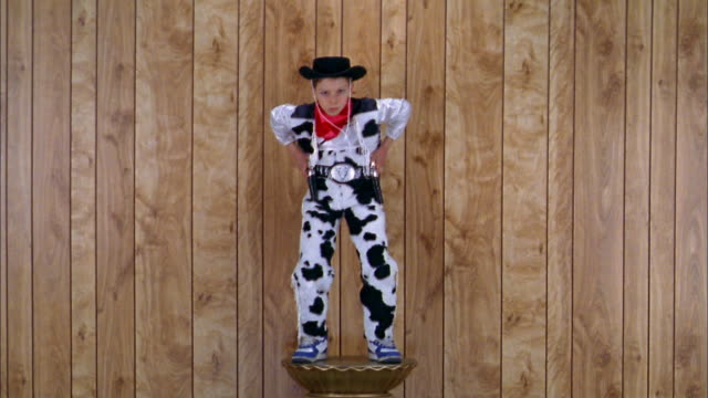 medium shot boy in cowboy costume on pedestal aiming toy pistols w/wood paneling in background - toy gun stock videos & royalty-free footage