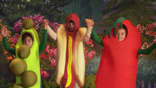 Medium shot boy in hot dog costume joining hands with girls in pea pod and carrot costume / taking bow on stage / curtain closing