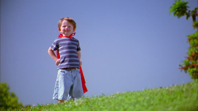Medium shot boy in red superhero cape standing on hill and smiling at CAM