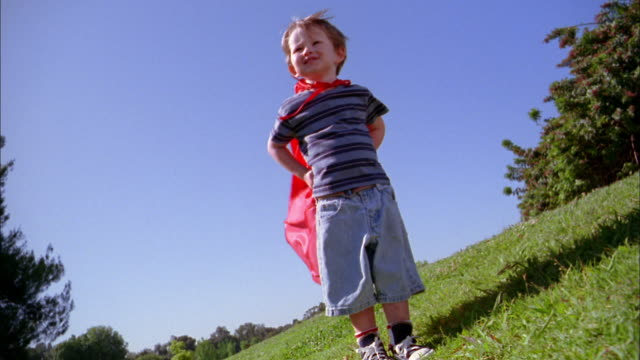 medium shot boy in red superhero cape standing outdoors and looking at cam w/cape blowing in wind - heroes stock videos & royalty-free footage