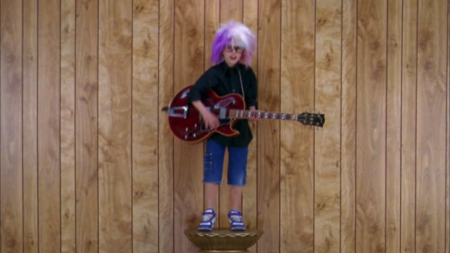 Medium shot boy in rock star costume on pedestal pretending to play electric guitar