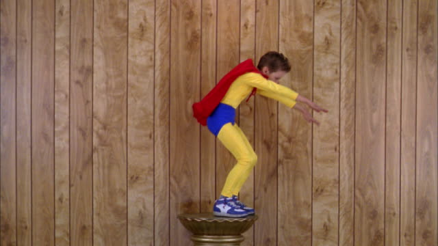 Medium shot boy in super hero costume standing on pedestal and pretending to fly