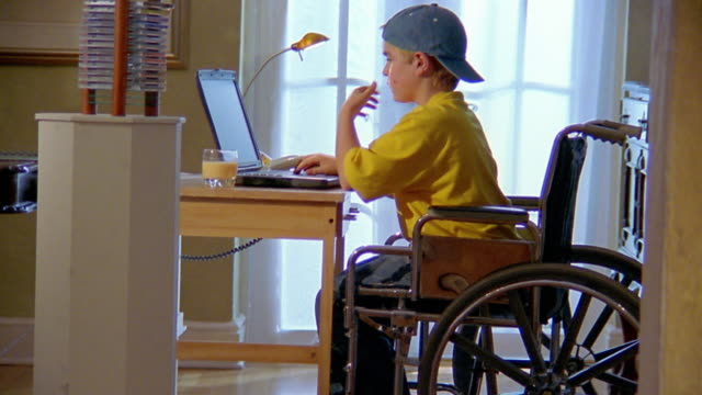 medium shot boy in wheelchair working on laptop / answering telephone - disability stock-videos und b-roll-filmmaterial