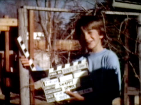 1983 medium shot boy in yard clapping film slate for home movie - anno 1983 video stock e b–roll