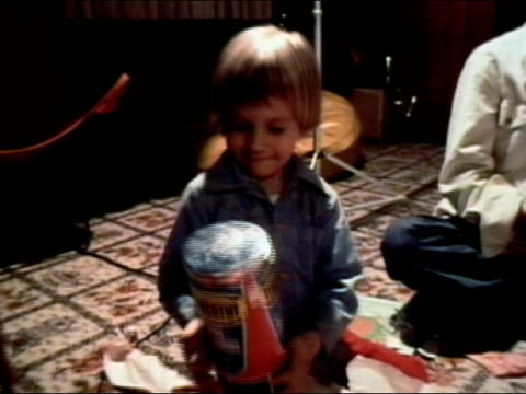 stockvideo's en b-roll-footage met 1977 medium shot boy opening hannukah gift of tinkertoys on floor - 1977