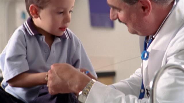 medium shot boy playing with doctor's id tag / el paso, texas - mindre än 10 sekunder bildbanksvideor och videomaterial från bakom kulisserna