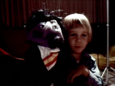 stockvideo's en b-roll-footage met 1977 medium shot boy playing with hand puppet - 1977