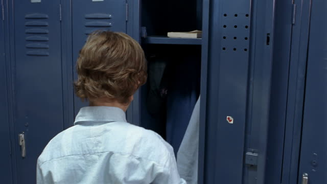 medium shot boy putting books into locker / getting shoved into locker by school bully - geek stock videos and b-roll footage