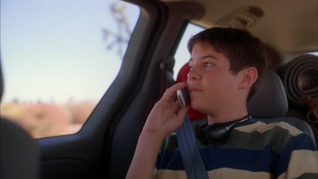 vídeos de stock, filmes e b-roll de medium shot boy sitting in minivan and speaking on mobile phone - só um menino adolescente