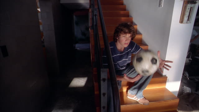 medium shot boy sitting on staircase and tossing soccer ball - 16歳から17歳点の映像素材/bロール