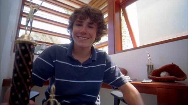 vídeos de stock, filmes e b-roll de medium shot boy sitting w/trophy on knee and smiling at cam - só um menino adolescente