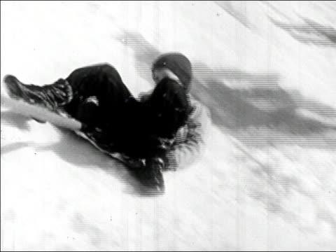 vídeos de stock e filmes b-roll de 1945 medium shot boy sliding down hill on snow shovel and rolling off/ audio - pá para neve