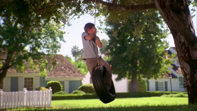 medium shot boy standing and spinning on tire swing in yard - tire swing stock videos & royalty-free footage