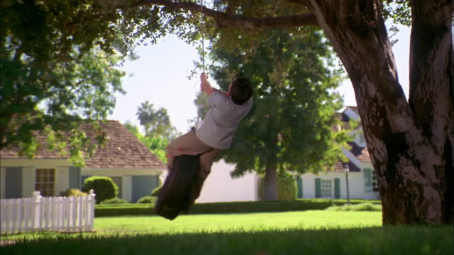 medium shot boy standing on tire swing in yard - tire swing stock videos & royalty-free footage