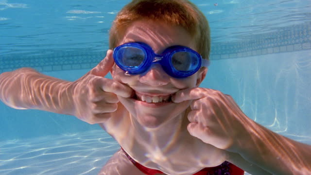 medium shot boy swimming underwater and making faces at camera - pulling funny faces stock videos & royalty-free footage