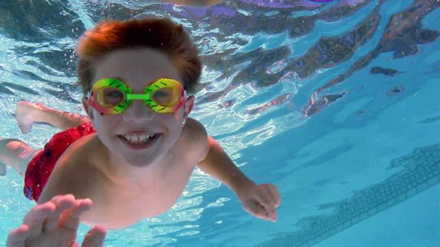 Medium shot boy swimming underwater and smiling at camera