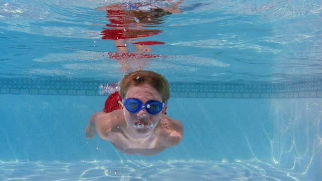 medium shot boy swimming underwater towards camera, smiling, and waving - swimming pool stock videos and b-roll footage