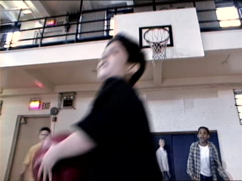 vidéos et rushes de medium shot boy throwing and catching ball during gym class dodgeball game/ zoom out wide shot boys in gym/ new york city - moins de 10 secondes