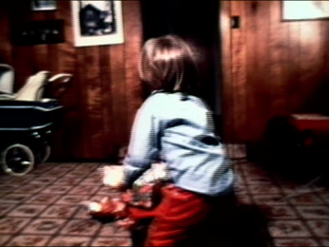 stockvideo's en b-roll-footage met 1977 medium shot boy with hannukah gifts in pile in on living room floor - alleen jongens