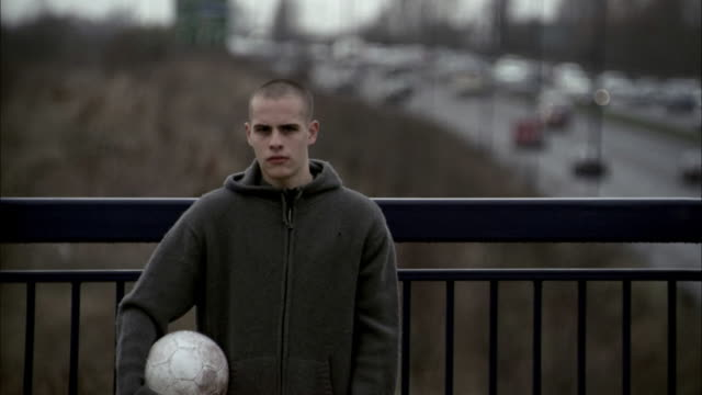 Medium shot boy w/soccer ball under arm looking at CAM