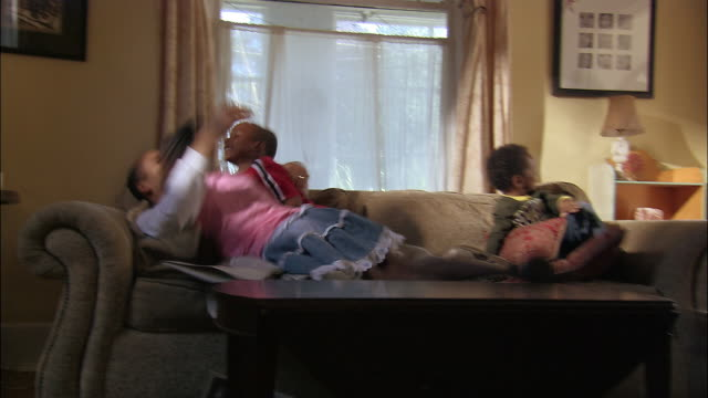 Medium shot boys and girl jumping / falling on top of father lying on couch
