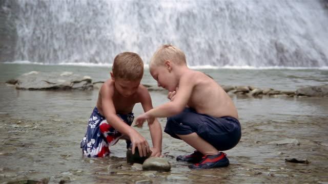 medium shot boys looking under rocks in stream at foot of waterfalls / stony brook state park, new york - badbyxor bildbanksvideor och videomaterial från bakom kulisserna