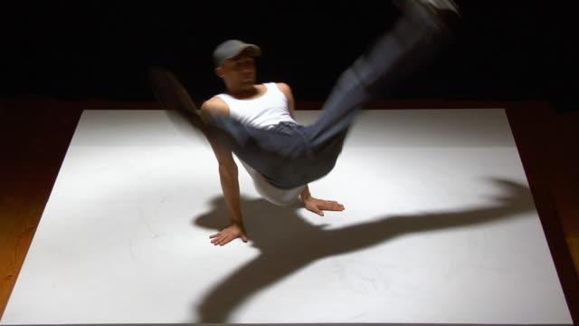 Medium shot breakdancer spinning on white floor