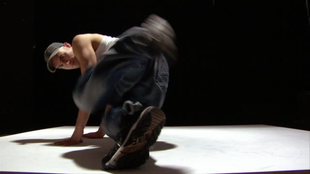 medium shot breakdancer spinning on white floor - baggy jeans stock videos & royalty-free footage