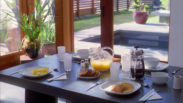 Medium shot breakfast place setting on table w/eggs and toast + coffee + juice + pancakes