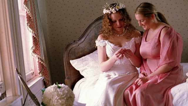 Medium shot bride and bridesmaid sitting on bed looking at locket necklace