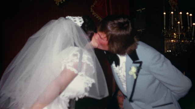 vídeos de stock e filmes b-roll de 1974 medium shot bride and groom kissing at wedding reception - 1974