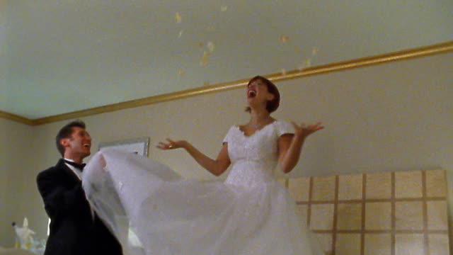 vídeos de stock e filmes b-roll de medium shot bride jumping on hotel bed / groom playing with her gown - noiva