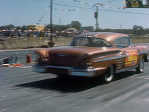 1959 medium shot bronze-colored car taking off from starting line and moving down race track