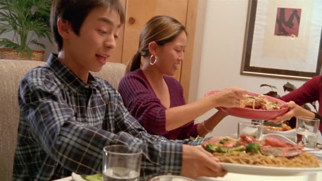 medium shot brother and sister taking + passing food around dining table during meal with family / honolulu - 麺点の映像素材/bロール