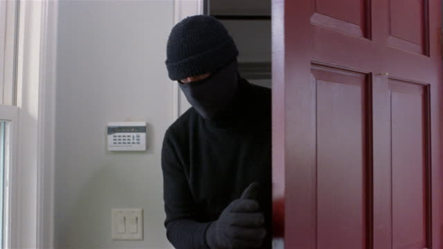 medium shot burglar wearing ski mask sneaking into house / burglar alarm on the wall - halbnahe einstellung stock-videos und b-roll-filmmaterial