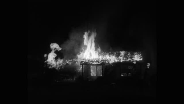 vídeos y material grabado en eventos de stock de medium shot burning house at night, men on horseback riding around it with torches - plató de cine