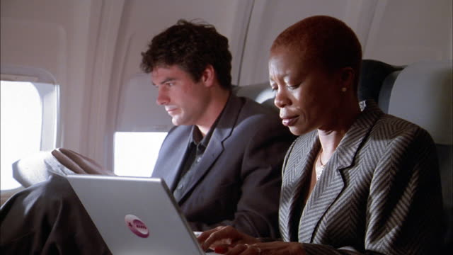 Medium shot businessman and businesswoman working on laptops on airplane / woman showing man screen / laughing