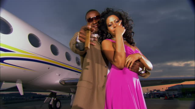 medium shot businessman and diva embracing on runway near private airplane / long beach, california, usa - vanity stock videos & royalty-free footage